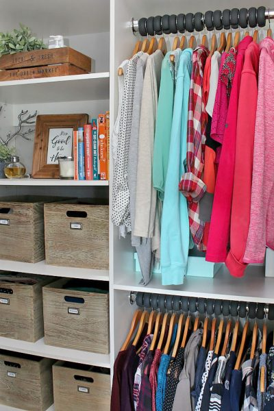 Organized closet with clothes arranged by color.
