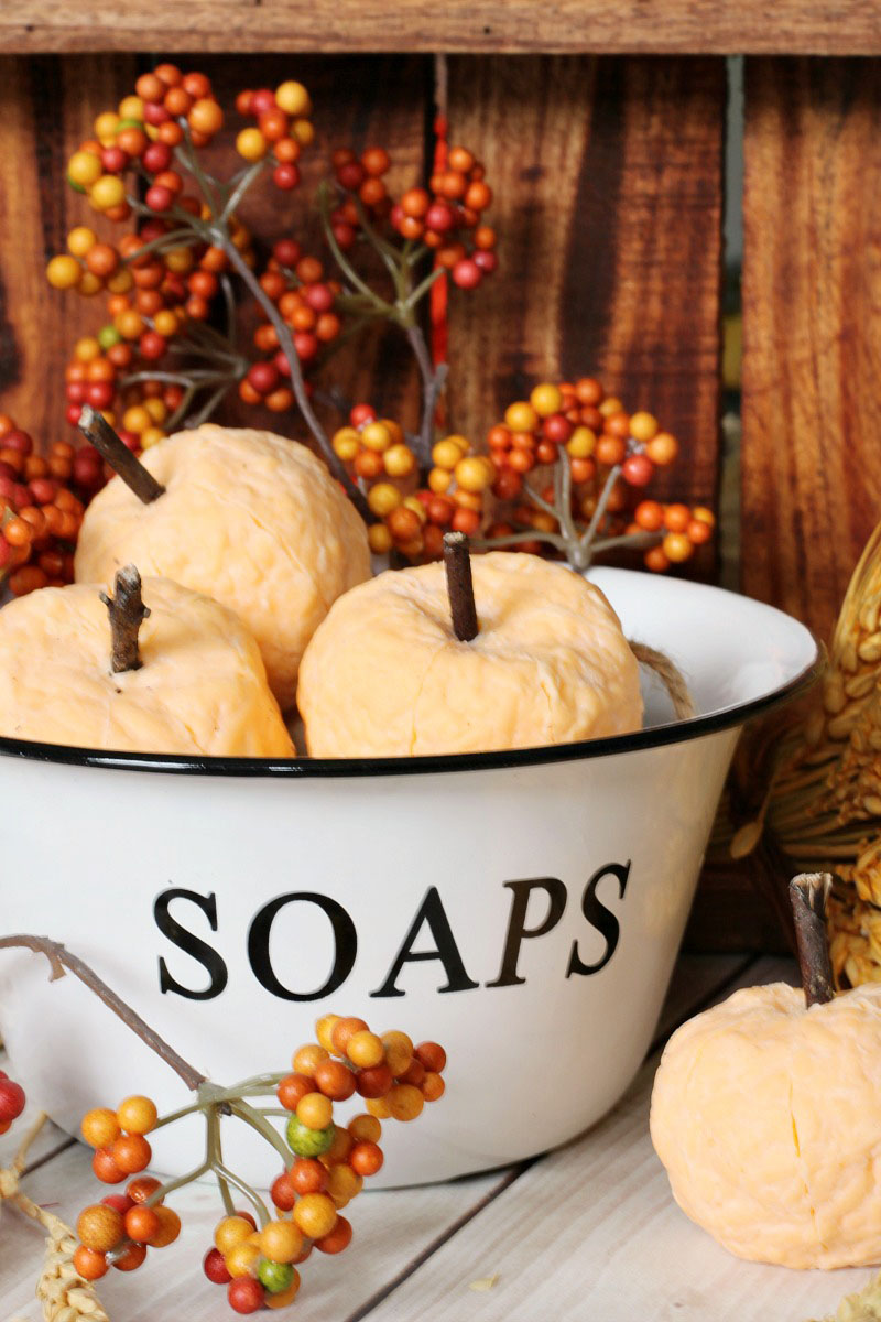 Cute DIY pumpkin soaps in a white enamel soap dish.