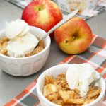 Bowls of slow cooker apple crisp topped with ice cream.