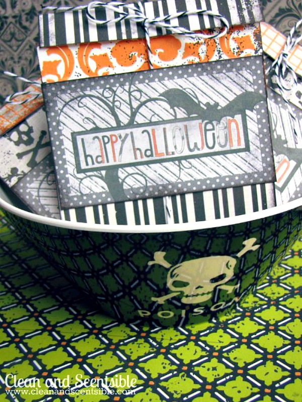 Store-bought Halloween candy packaged up as customized Halloween treats using free printable Halloween tags. Displayed in a Halloween bowl.
