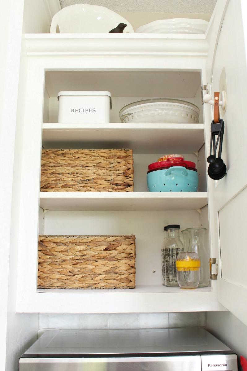 Organized kitchen cabinet with baskets.