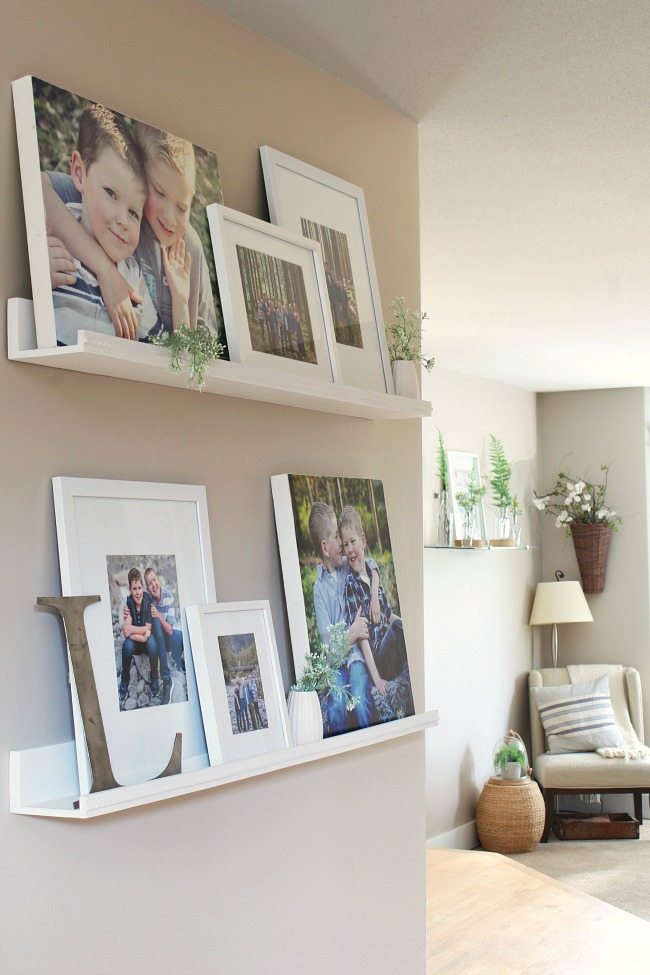 Pretty photo gallery wall using photo ledges to cover up an ugly thermostat.