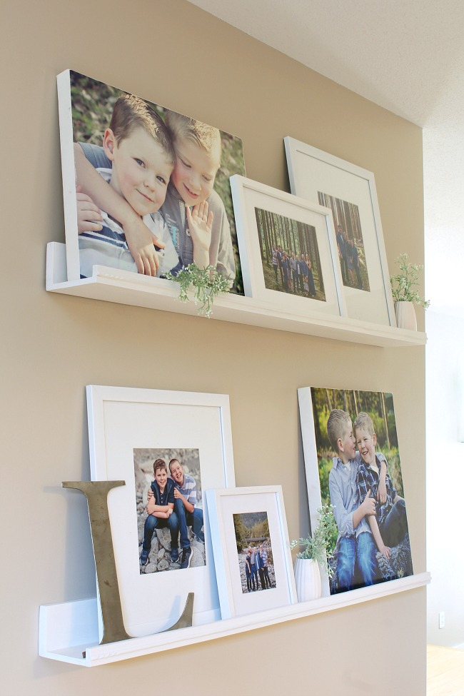 Photo gallery wall using photo ledges to cover up an ugly thermostat.