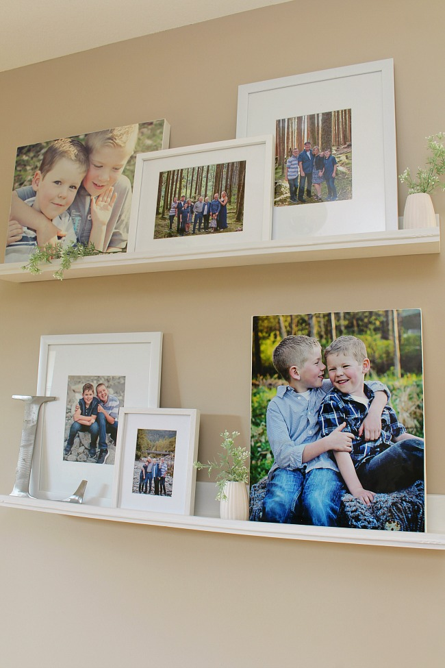 Photo gallery wall using photo ledges and a canvas photo frame to hide a thermostat.