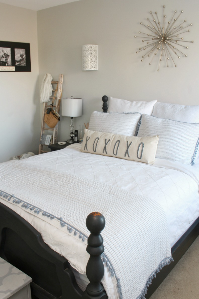 Black farmhouse style bed frame with white bedding and blue accents.