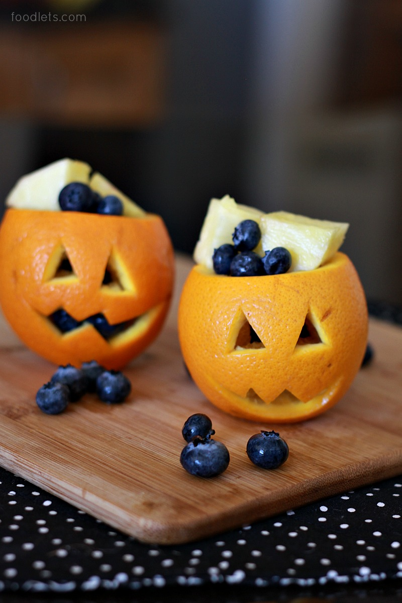 Halloween Jack-o-lantern fruit cups made from oranges and filled with various fruit.