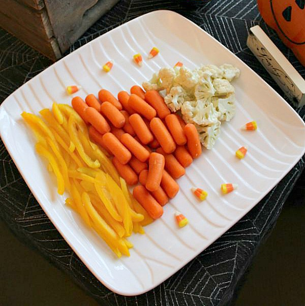 Fun and healthy Halloween food ideas. Candy corn veggie platter made from cauliflower, carrots, and yellow peppers.