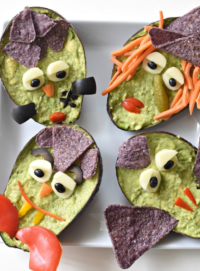 Guacamole monsters in an avocado decorated with a variety of vegetables.