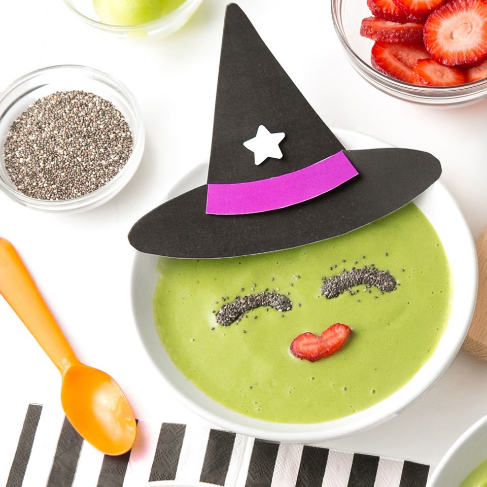 Healthy Halloween food ideas. Witch smoothie bowl using green smoothie and a paper witch hat.