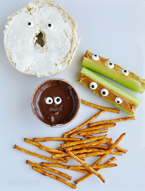 Fun and healthy Halloween snack ideas. Halloween candy eyes added to a number of snack ideas - cream cheese and bagel, pudding dip with pretzels, and peanut butter and celery sticks.