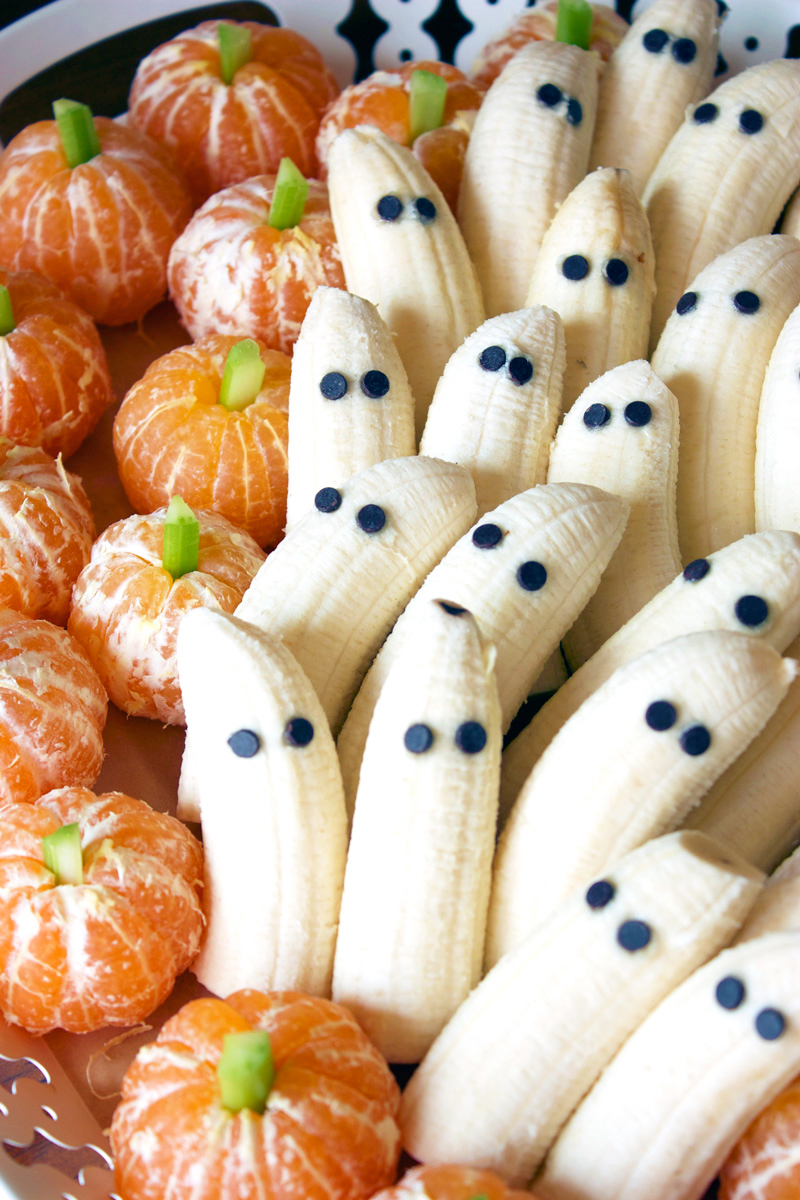 Platter of healthy Halloween snack ideas - tangerine pumpkins and banana ghosts.