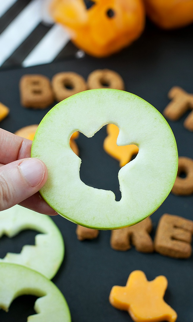 Healthy Halloween Food Ideas. Halloween apple slices using halloween cookie cutters to cut out Halloween shapes.
