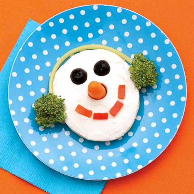 Cute snowman Christmas snack made from a bagel and cream cheese.