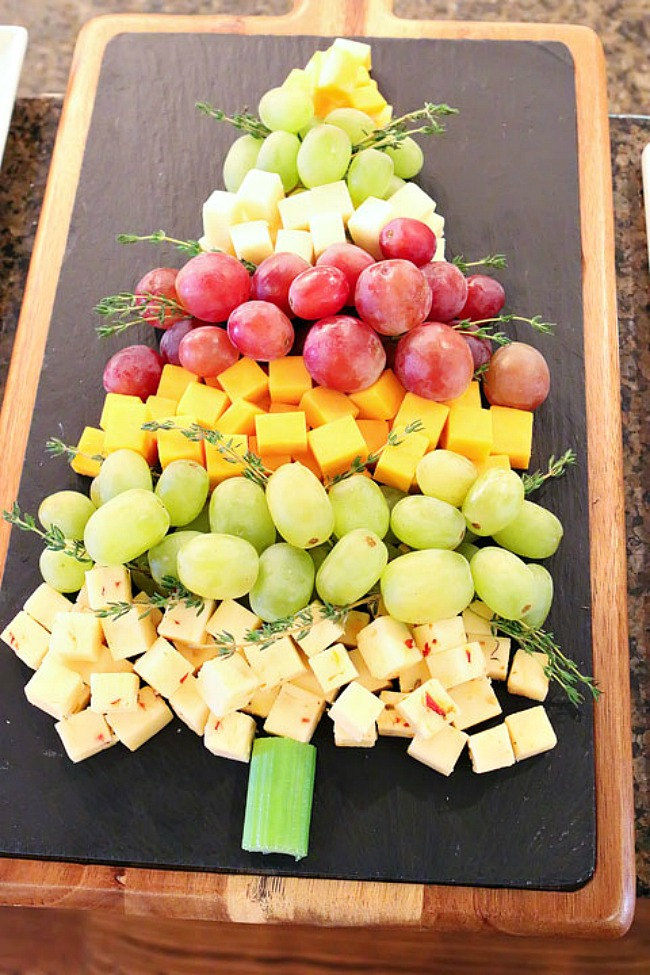 Christmas tree cheese tray using various cheeses and grapes.