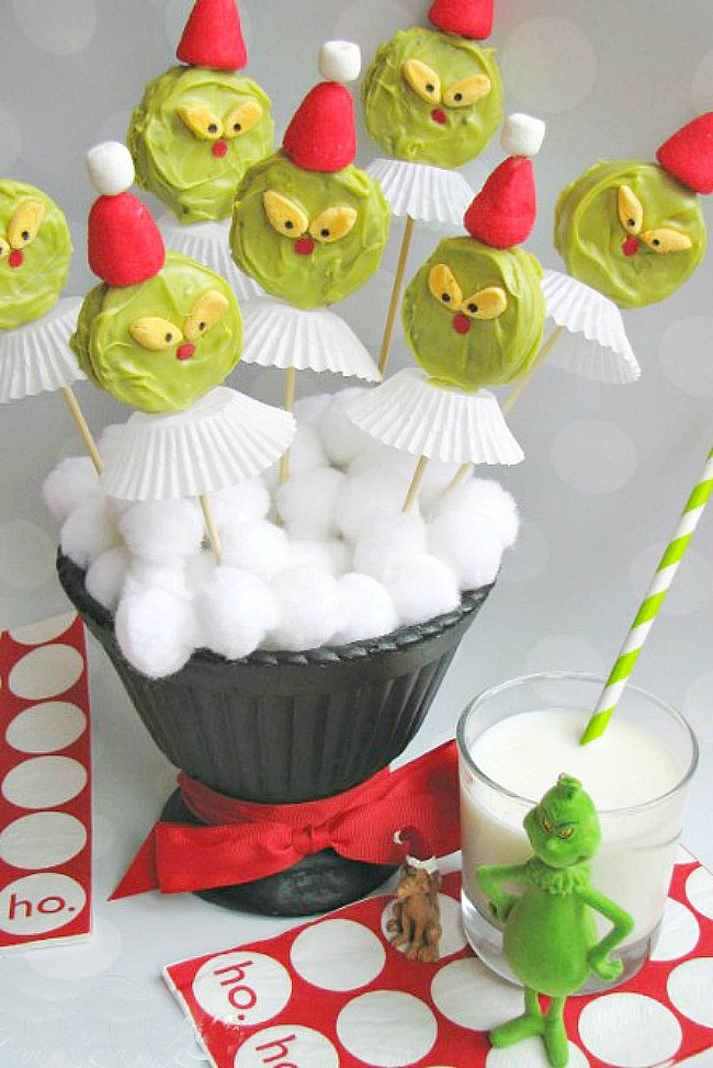 Grinch Oreo pops displayed in a vase with white pom poms.