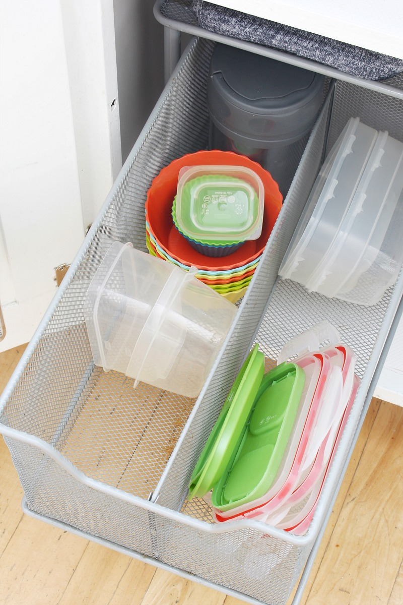 Pull out kitchen organizer drawer to store smaller containers, lids and kids' water bottles.