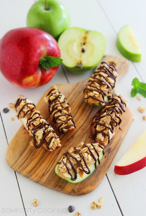 Apple slices topped with granola, chocolate drizzles, and peanut butter.