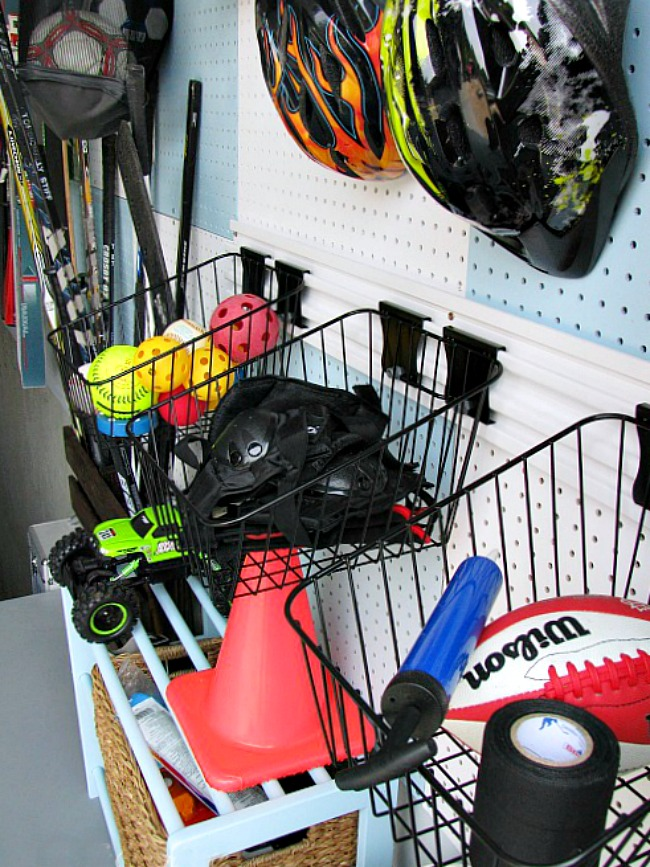Pegboard organizer with baskets to store sports equipment.