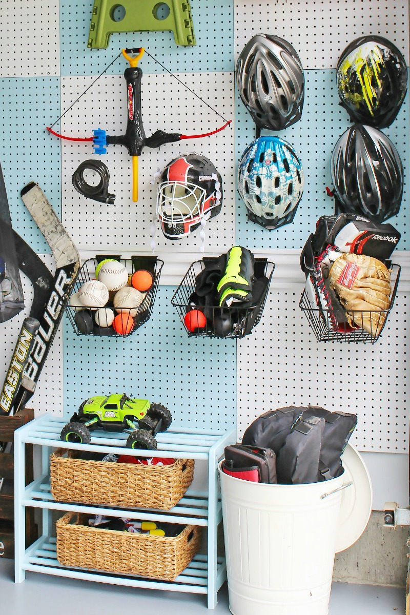 Blue and white checked pegboard organizer for sports equipment.