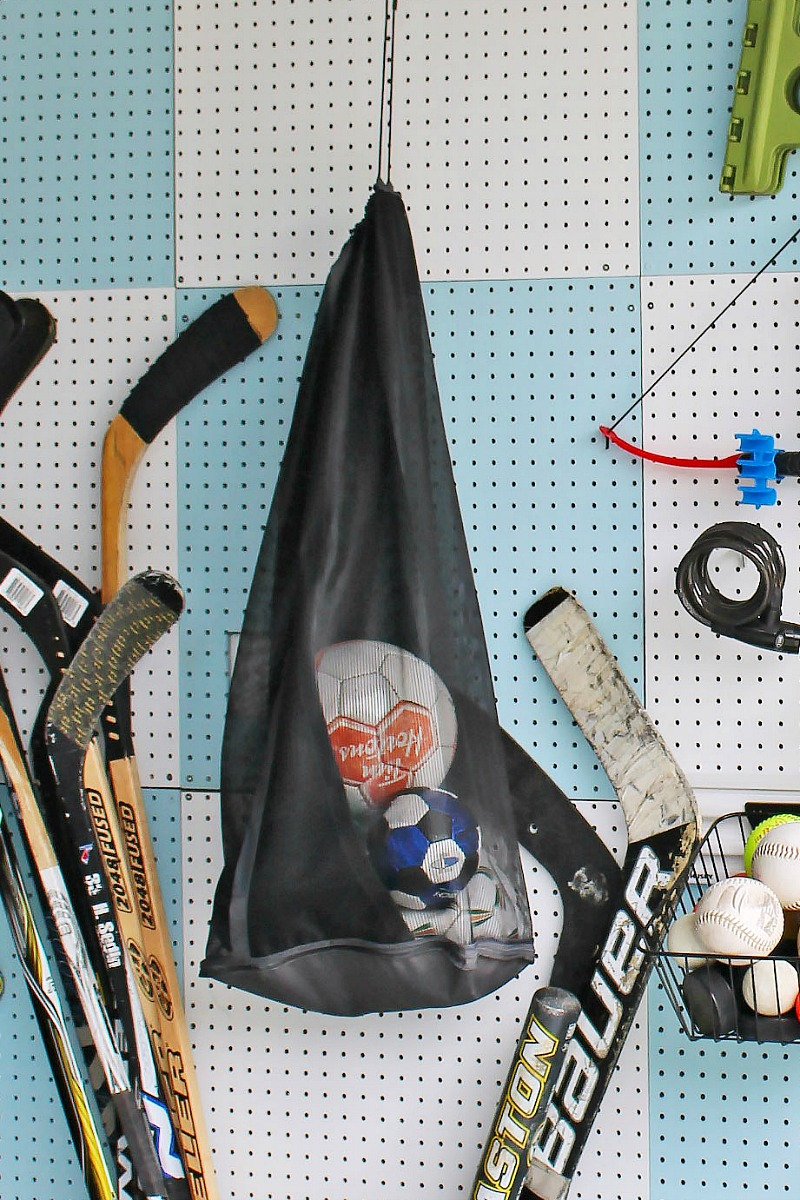 Pegboard organizer with hanging ball bag to store balls.