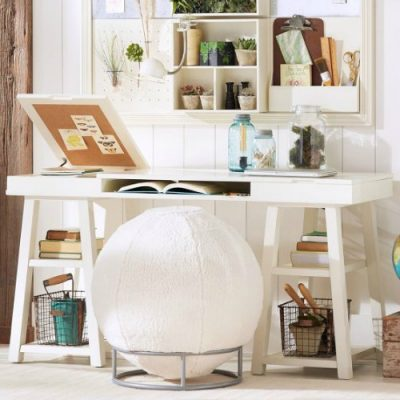 White desk with an exercise ball to sit on.