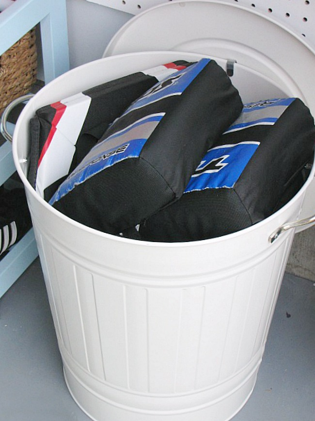White metal garbage can used to store street hockey pads.