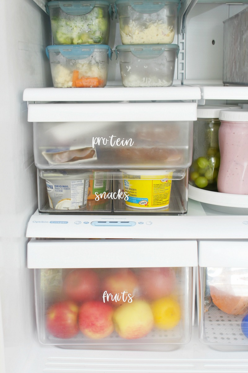 Clean and organized fridge with labelled bins and baskets.