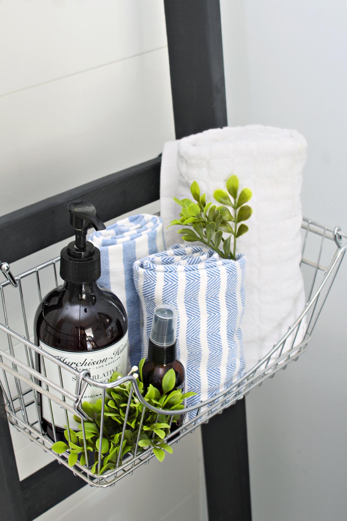 Black DIY bathroom storage ladder with wire baskets.