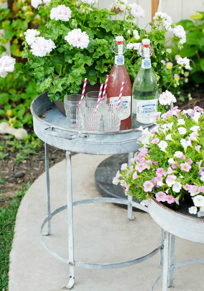 Pretty galvanized tables used as planters and a small beverage bar.