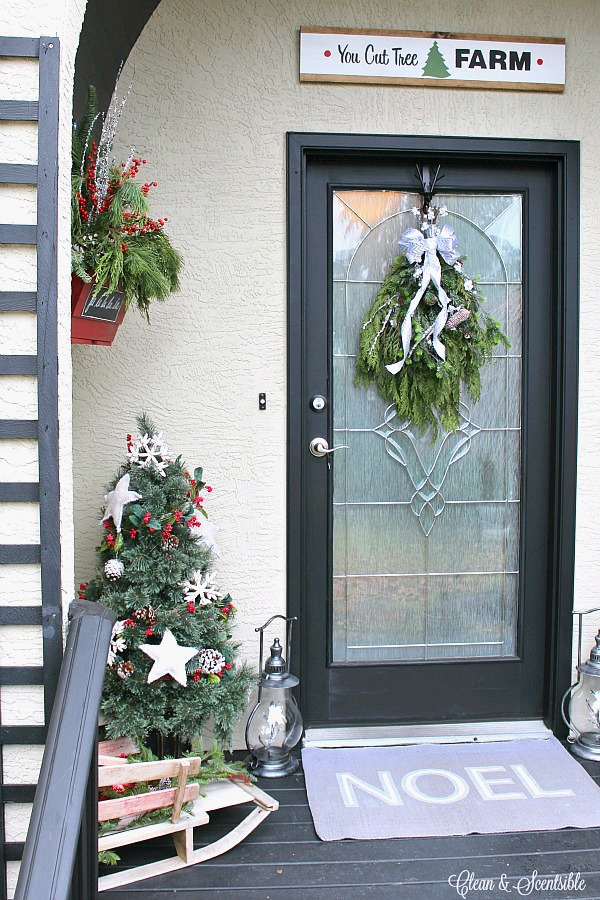 Rustic Christmas front porch with a DIY swag Christmas wreath on the door.