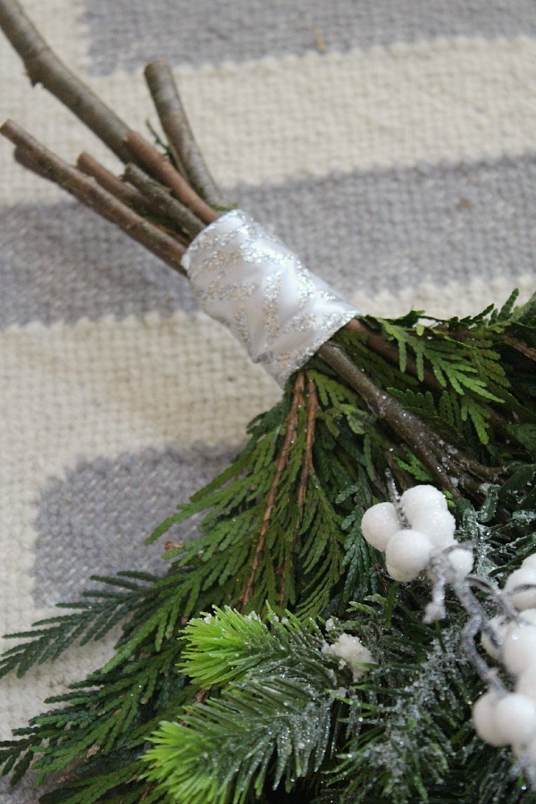 Simple step by step tutorial to create a DIY Christmas swag wreath.  Wrap ribbon around the ends to hide duct tape.