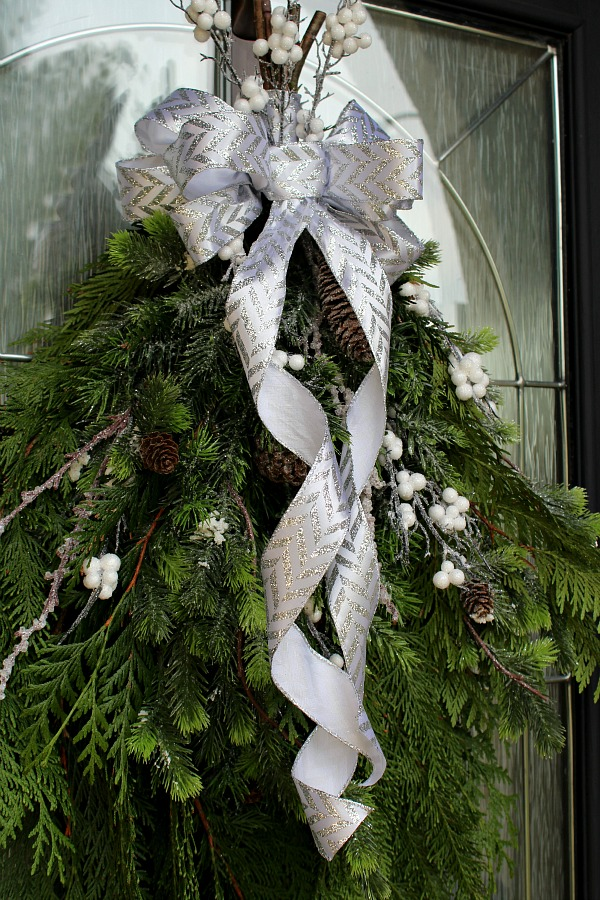 Simple DIY Christmas swag wreath made from fresh greenery with a pretty ribbon bow.