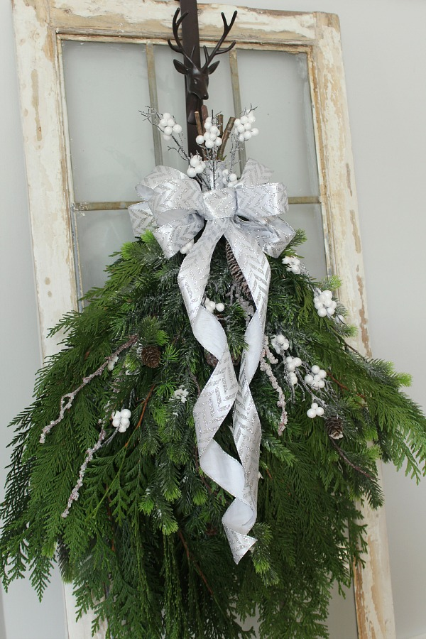 Simple DIY Christmas Wreath with fresh greenery hanging on a vintage window. So pretty!