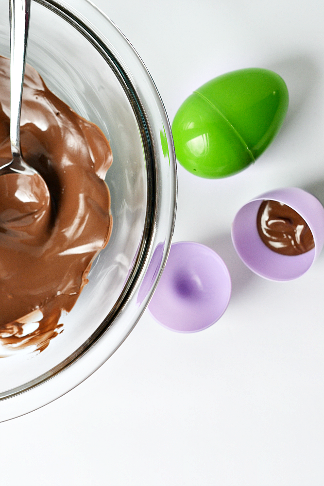 DIY chocolate confetti Easter eggs step by step instructions. Add melted chocolate to plastic Easter eggs and gently swirl around to distribute evenly.