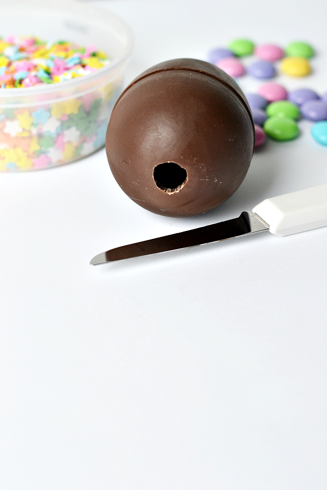 DIY chocolate confetti Easter eggs step by step instructions. Cut a small hole in the end of the chocolate egg to fill with treats.