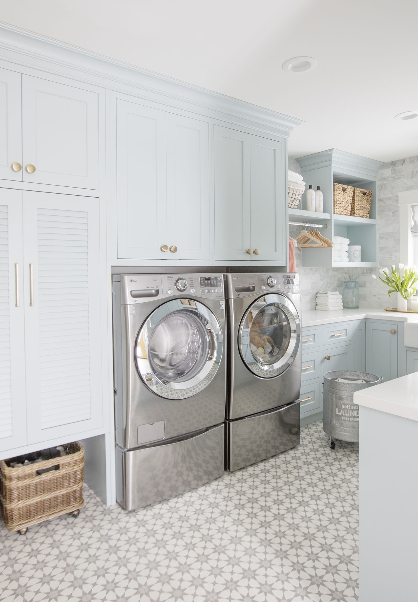 Beautiful laundry room design with light blue cabinets and stainless steel washer and dryer.