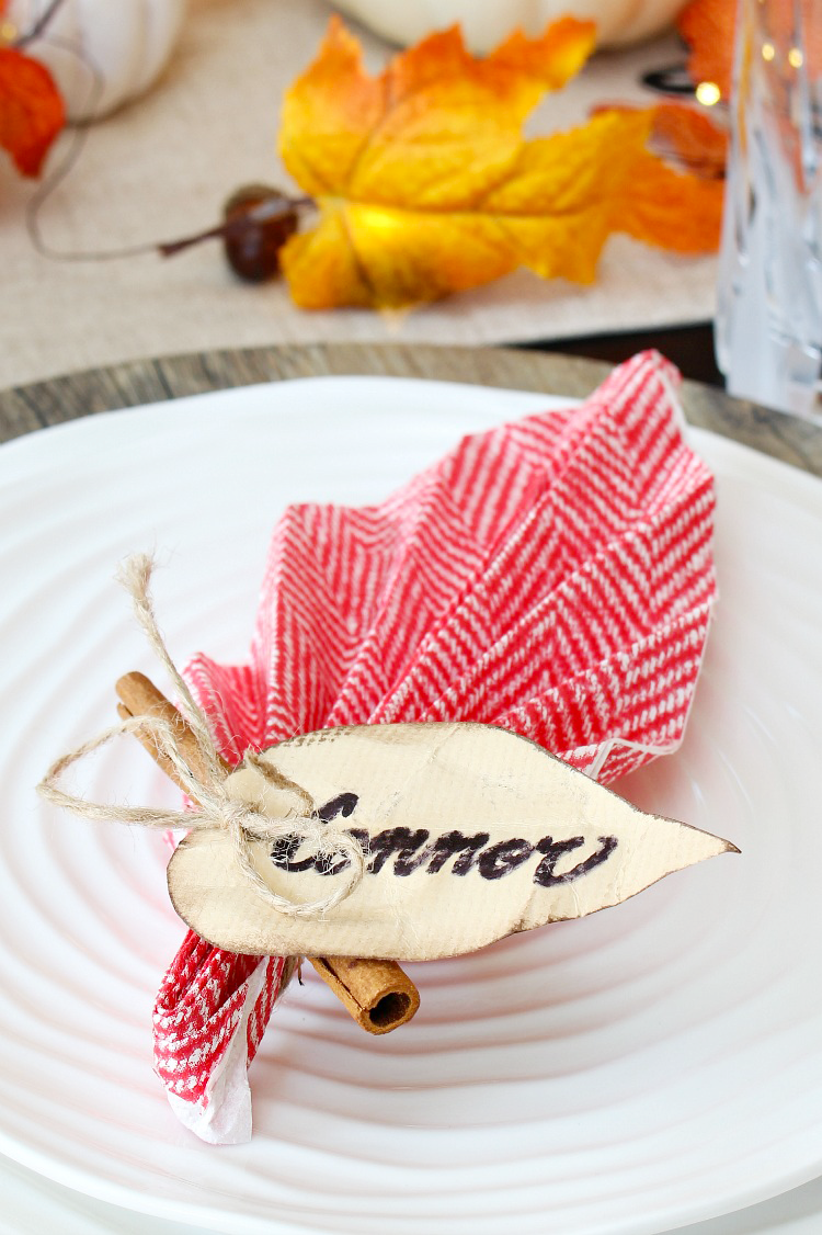 Fall leaf napkin folding with a cinnamon stick for a fall or Thanksgiving place setting.