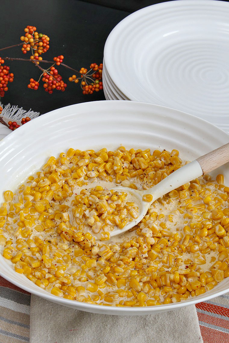 Slow cooker creamy corn in a white bowl.