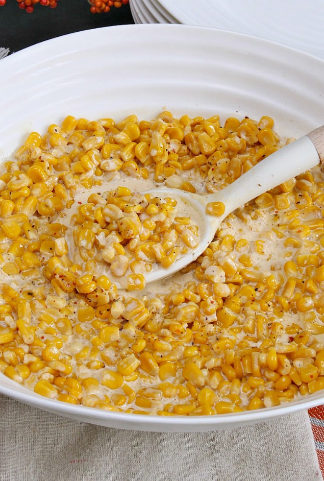 Delicious slow cooker creamed corn served in a white bowl for a holiday meal.