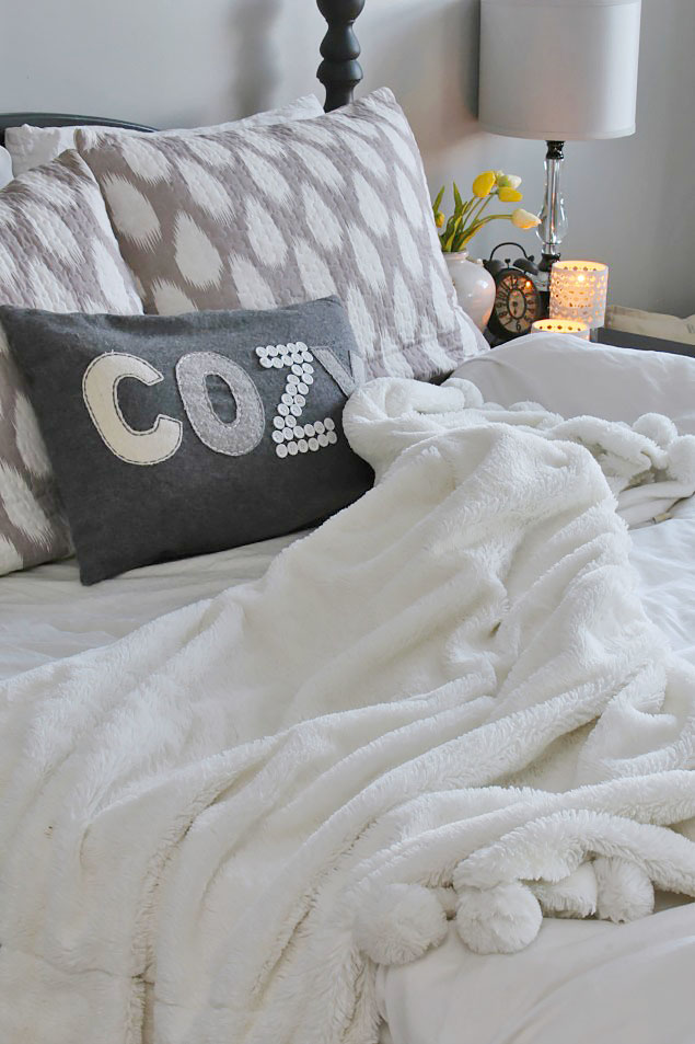 Cozy bed with white bedding, soft pom pom blanket, and a cozy pillow.