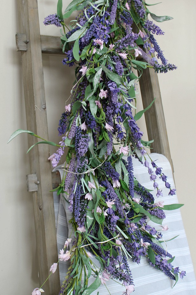 Beautiful spring decorating ideas using faux flowers. Lavender swag on a rustic farmhouse style ladder.