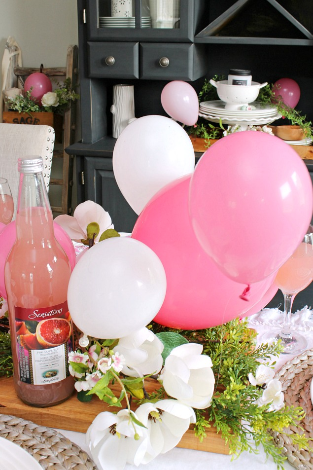 Pink balloon centerpiece with faux flowers and greenery.