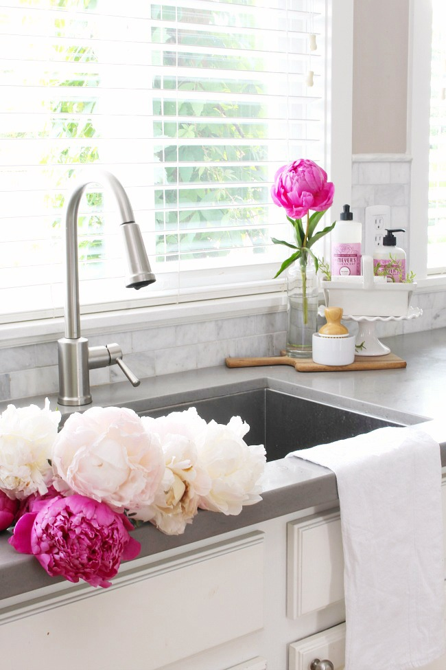Pink peonies in a white kitchen.