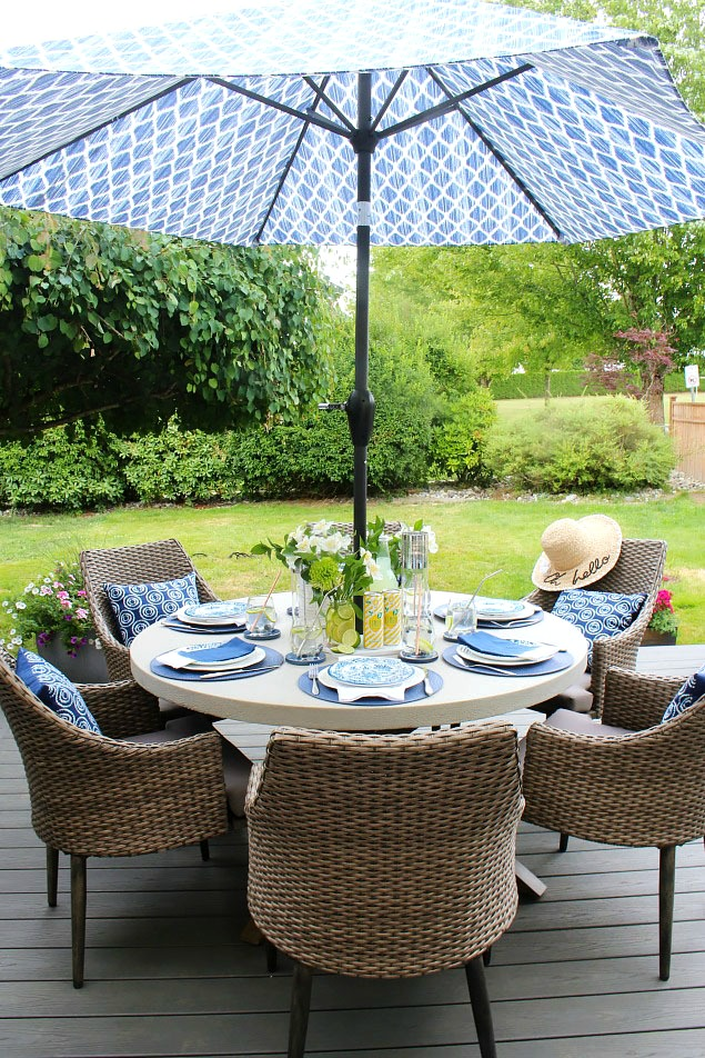 Round summer patio table. Summer tablescape with blues, greens, and yellows.