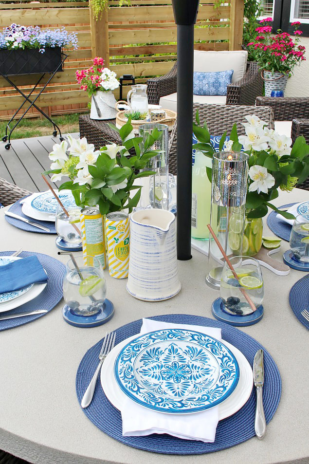 Pretty summer patio table decorated with blue and white dish ware and pops of yellow and green.