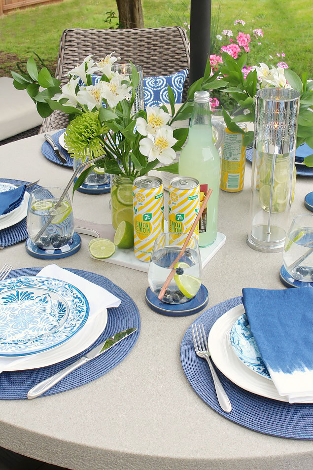 Summer tablescape with blue dishware and pops of green and yellow.