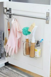 Use a towel bar or adhesive containers to attach to inside to kitchen cupboards for extra storage.