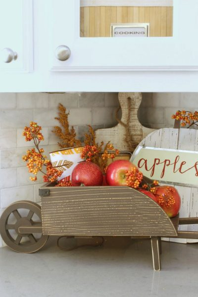 Easy fall kitchen decorating ideas. Simple ways to add some fall to your kitchen decor! Fill a small wheelbarrow with apples or other fruit for a seasonal display.