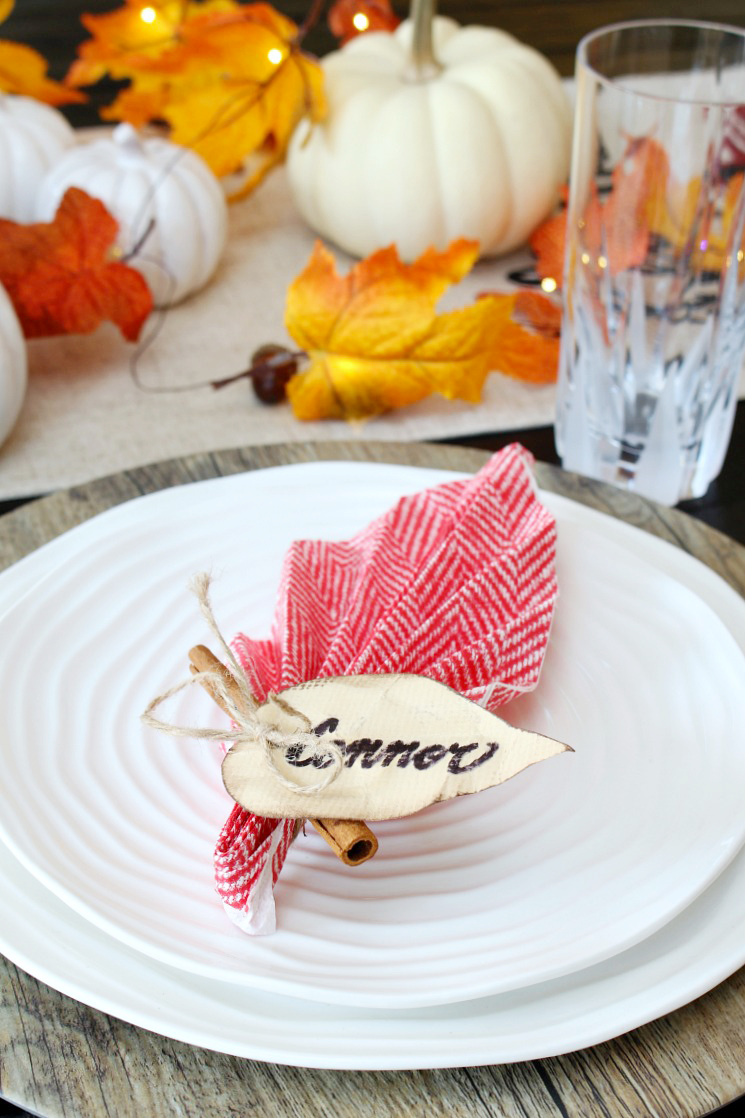 Paper napkin folded into a leaf for a fall or Thanksgiving tablescape.