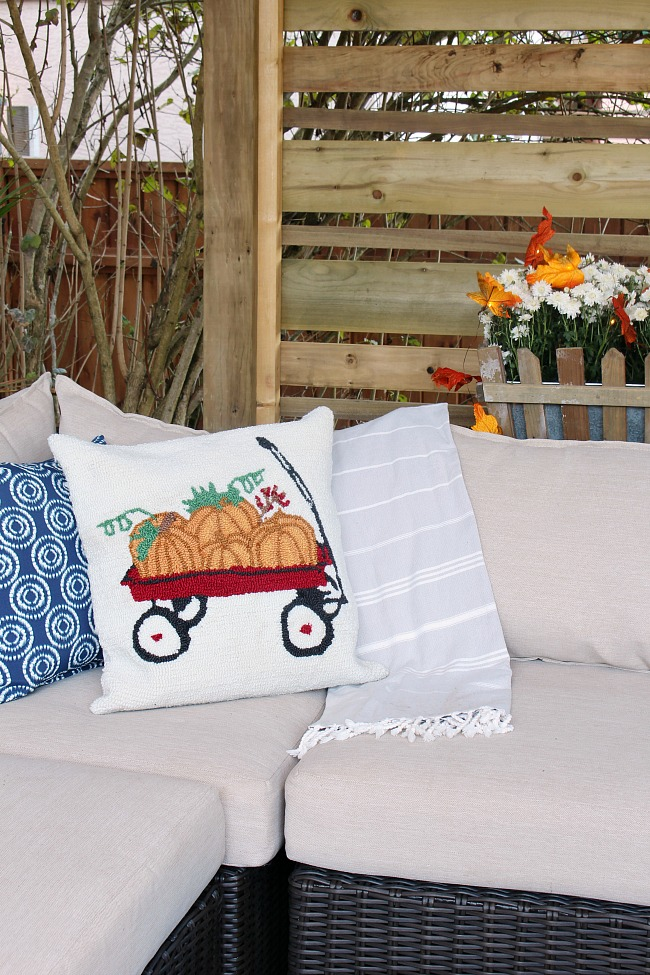 Fall Patio Design. Cute fall pillow with wagon and pumpkins.